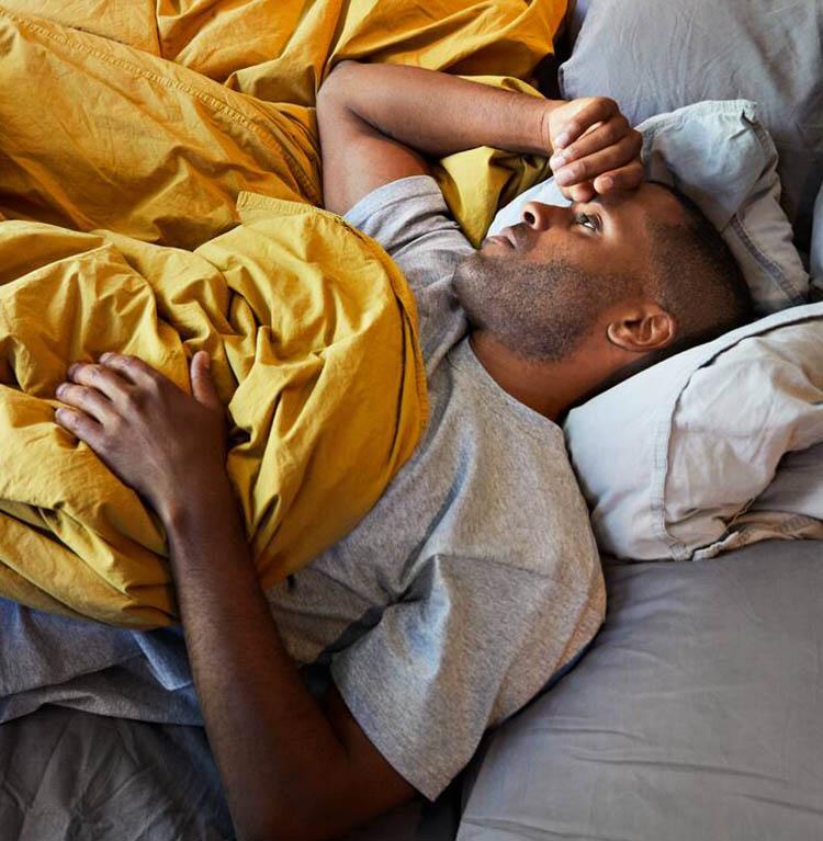En person ligger sjuk i sängen. Foto.