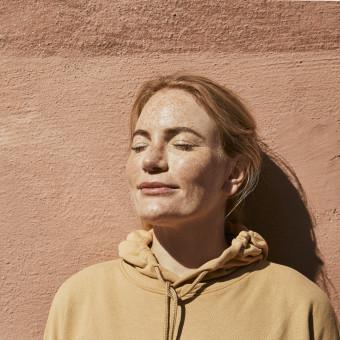 Kvinna med fräknar solar mot vägg. Foto.