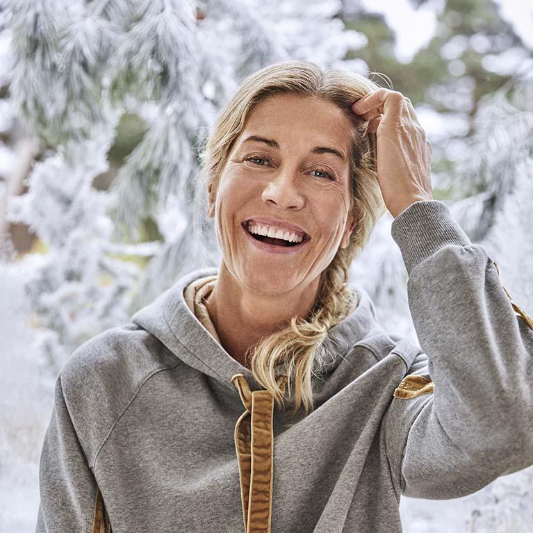 Glad kvinna i snöigt landskap