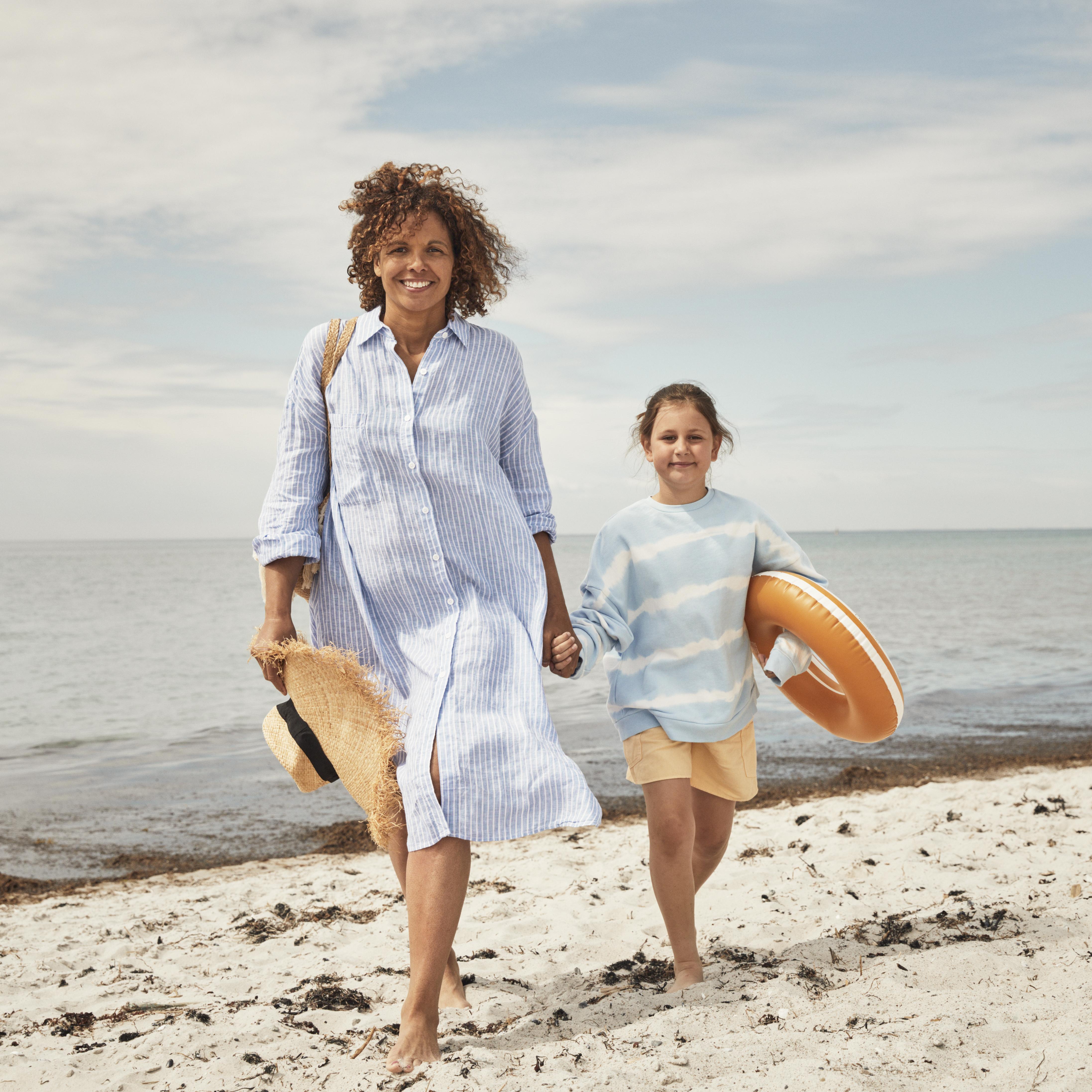 Mamma och dotter på strand. Foto.