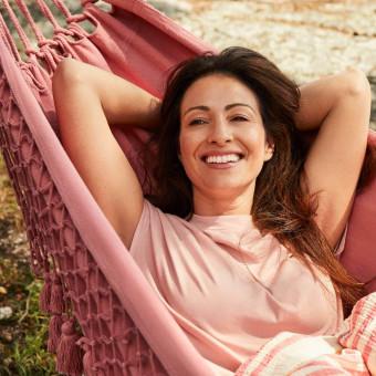 En leende person vilar i en hängmatta med händerna bakom huvudet. Foto.
