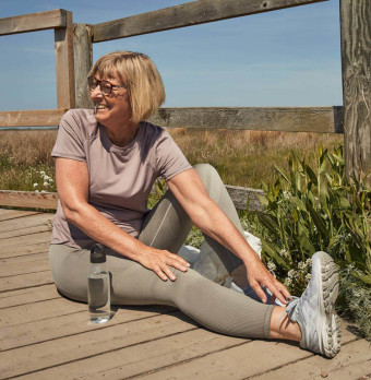 En äldre person  i träningskläder stretchar. Foto.