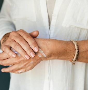 En person med ett armband smörjer händerna. Foto.