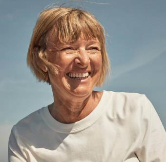 En äldre person ler brett. Foto.