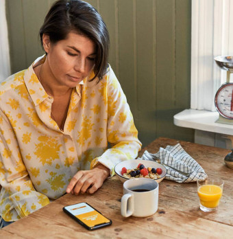 En person sitter vid en orörd frukost och läser på sin mobil. Foto.