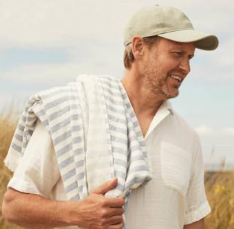 En leende person med keps vid stranden. Foto.
