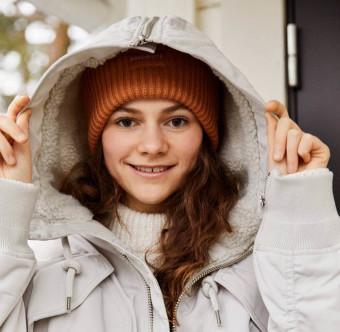 En tjej med vinterkläder ler brett. Foto.