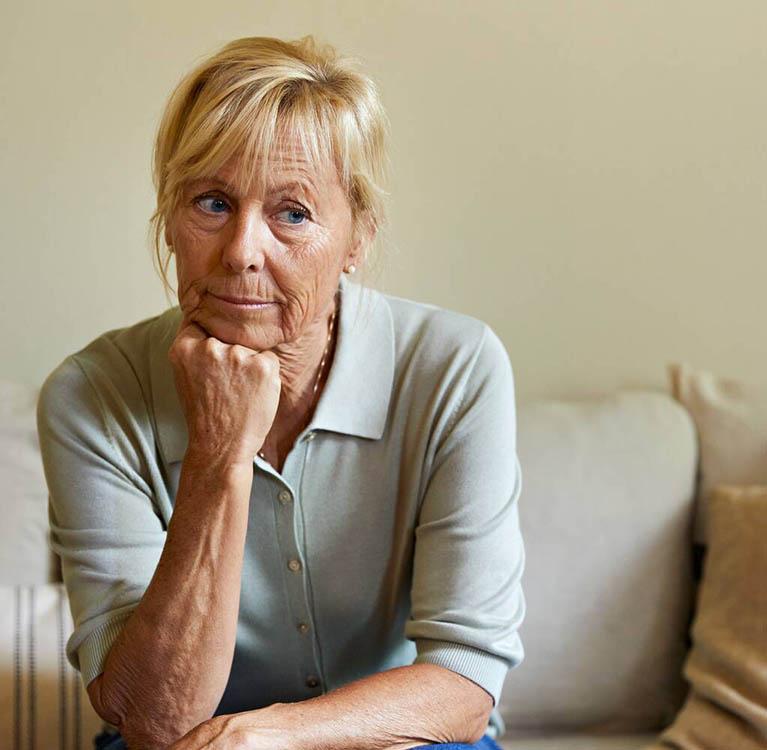 En äldre kvinna ser fundersam ut. Foto.