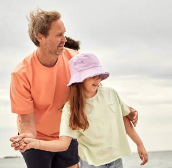En man och en dotter på stranden. Foto.