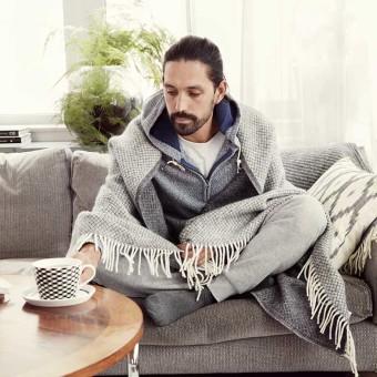 Man sitter i soffa med filt