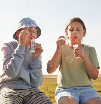 Två barn blåser såpbubblor tillsammans. Foto.
