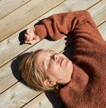 En person ligger på rygg på ett trägolv och blundar. Foto.
