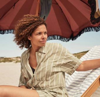 En kvinna sitter under ett parasoll på stranden. Foto.
