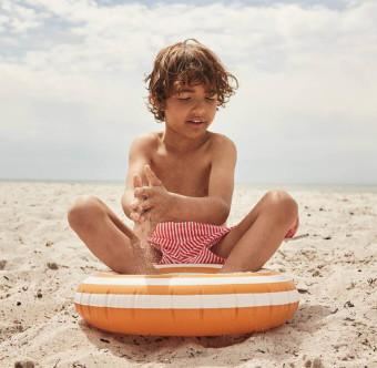 Ett barn leker i sanden på en strand. Foto.