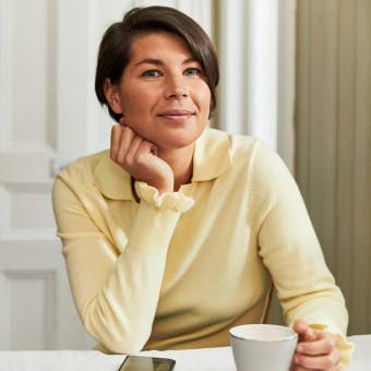 En person sitter med en kopp kaffe och ler