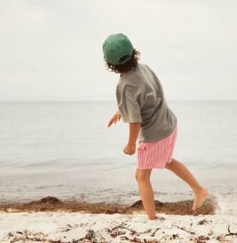Ett barn leker vid en strand. Foto.