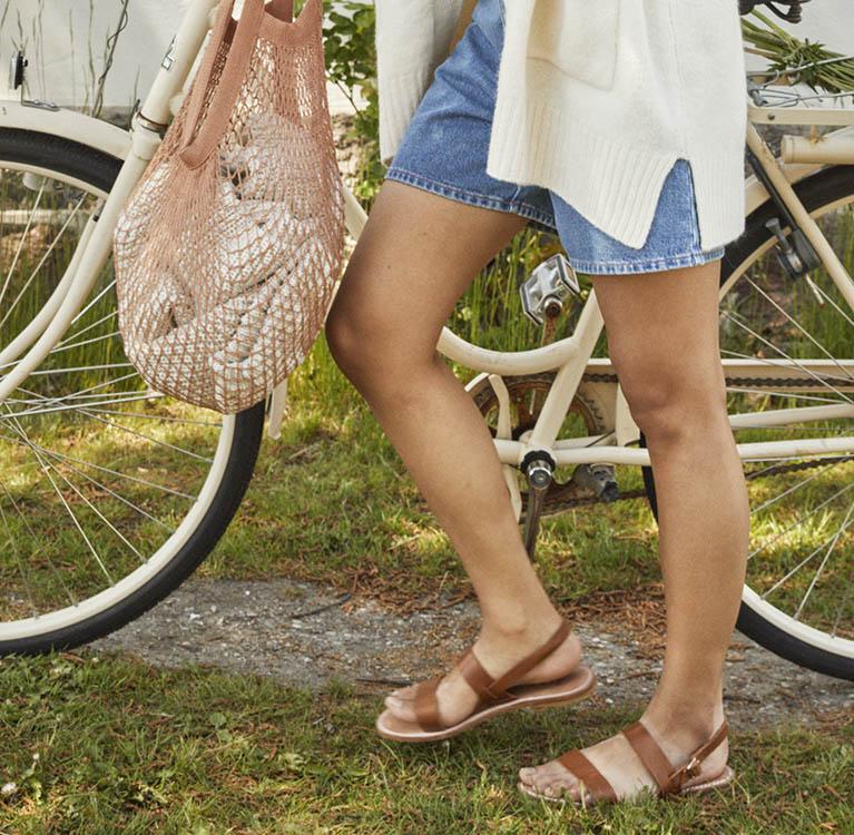 Närbild på en persons bara ben en somrig dag. Foto.