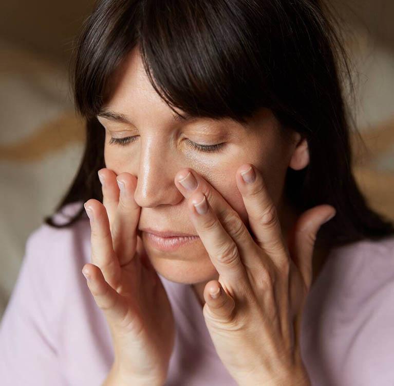 En kvinna rengör ansiktet. Foto.