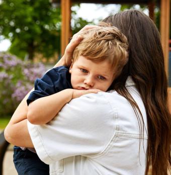 En kvinna tröstar en trött pojke. Foto.