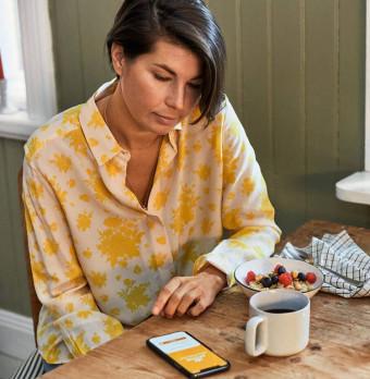 En kvinna i pyjamas läser på sin telefon vid köksbordet. Foto.