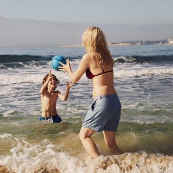 Kvinna och barn leker i vattnet på sommaren. Foto.