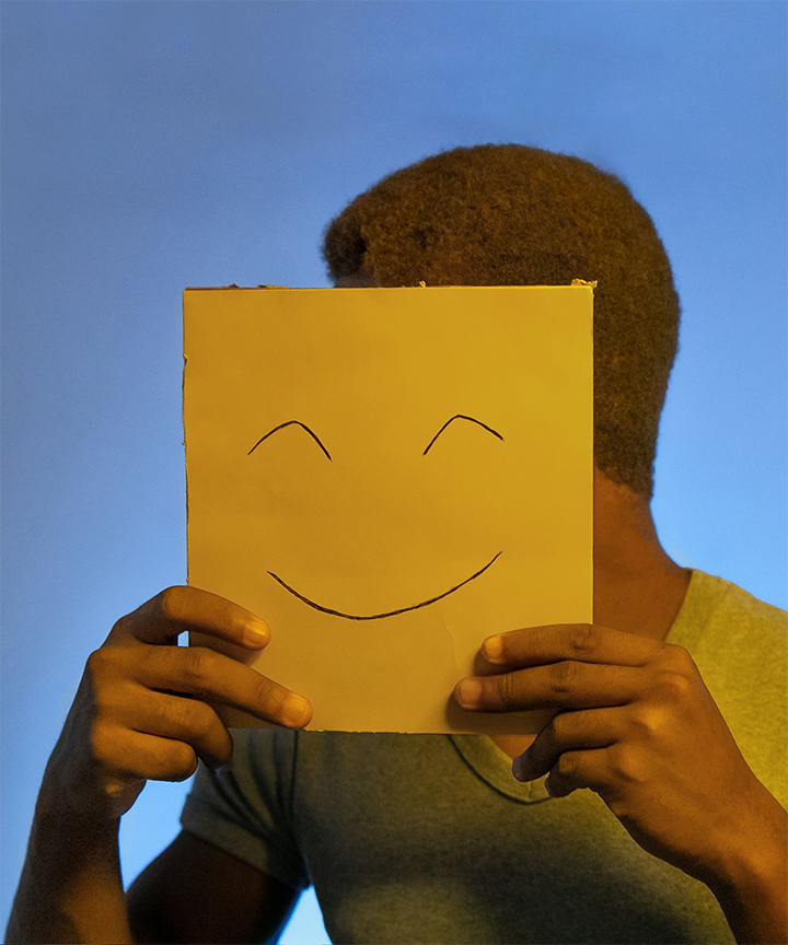 Black man wearing yellow shirt covering his face with a yellow piece of paper. The paper has a smile drawn on it. The sky is blue.
