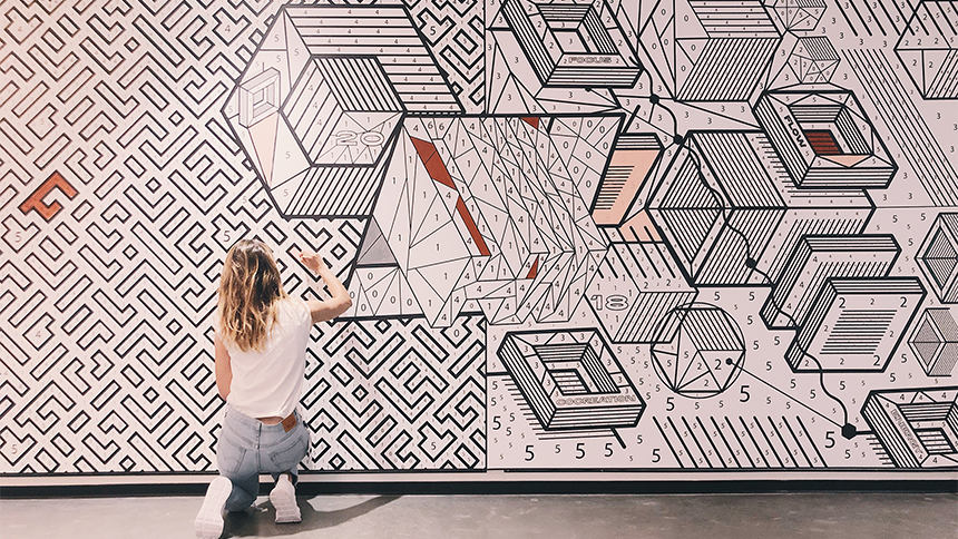 Emma painting a geometric mural.