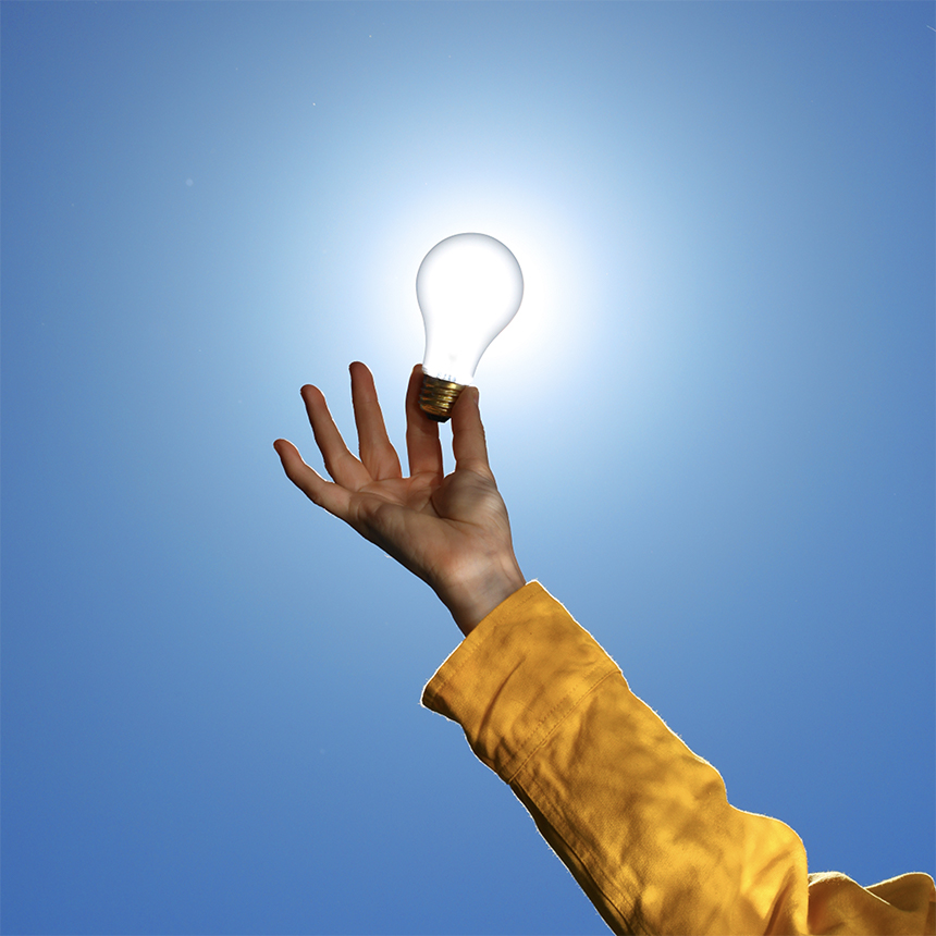 A hand holding the lightbulb up to the sun. The person is wearing a yellow shirt.