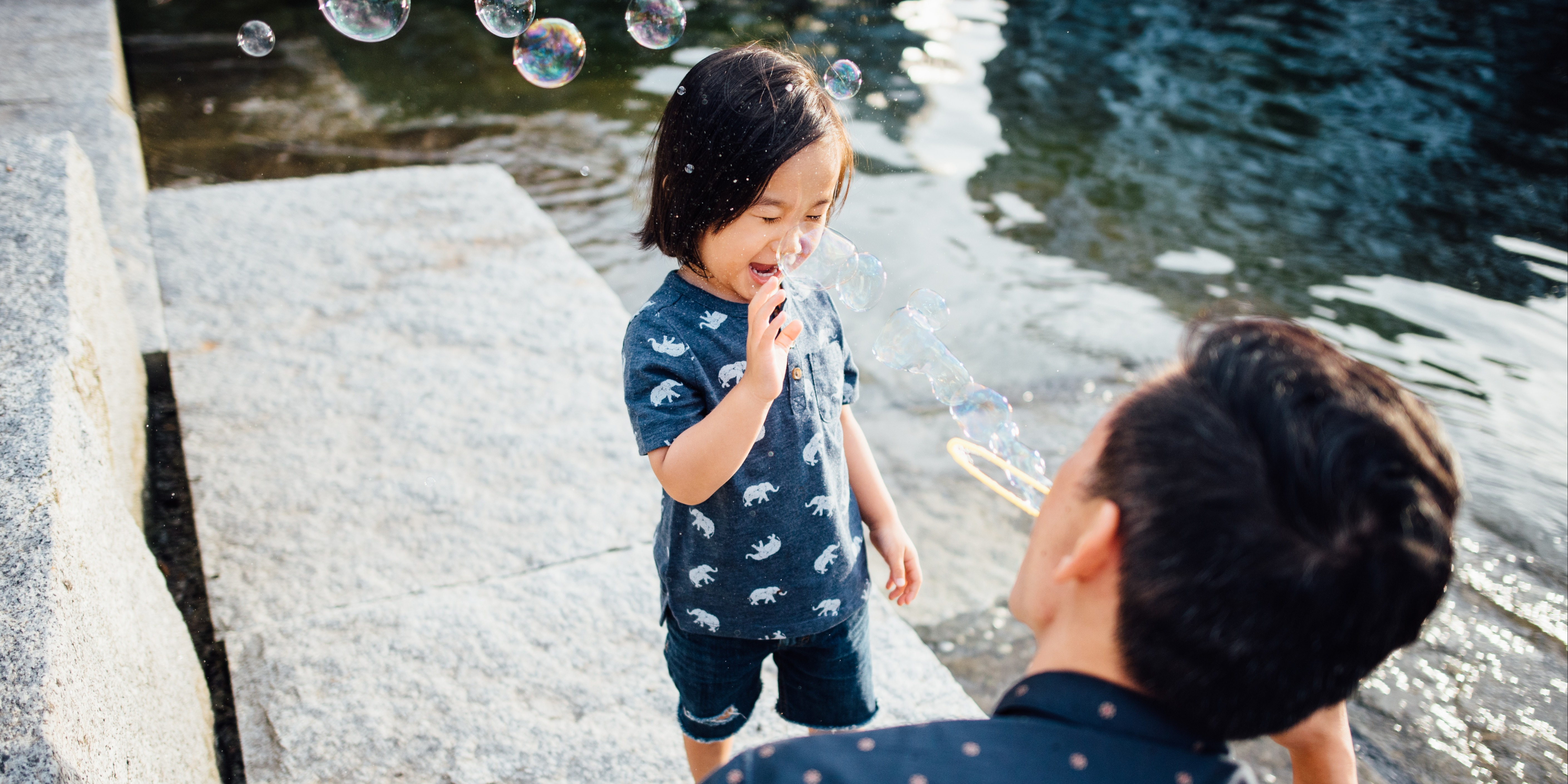 father and young son blowing bubbles together