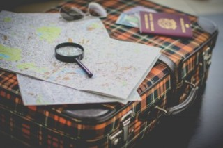 Map with a magnifying glass on top of a suitcase