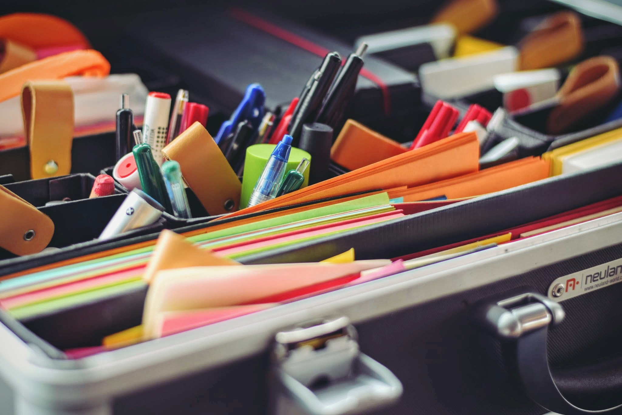 Photo of various office supplies, pens, coloured paper, scissors in green, black and orange