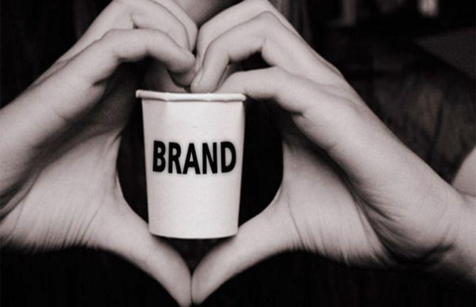 """Foto: Zwei Hände, die als Herz geformt sind, halten einen Becher, auf dem das Wort """"Marke"""" steht."""