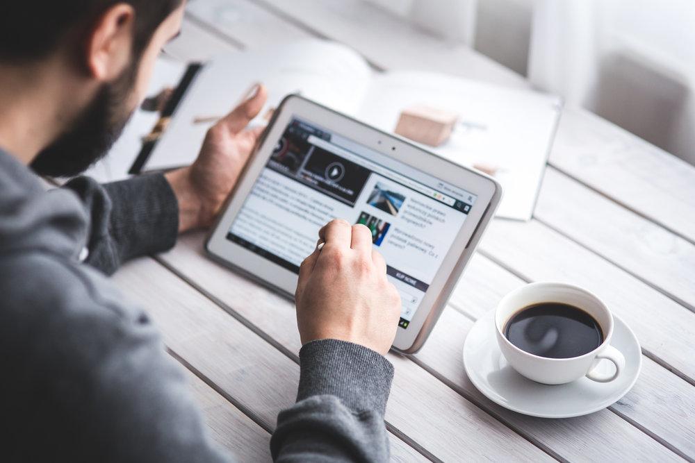 Foto: Ein Mann liest einen Artikel auf einem Tablet.