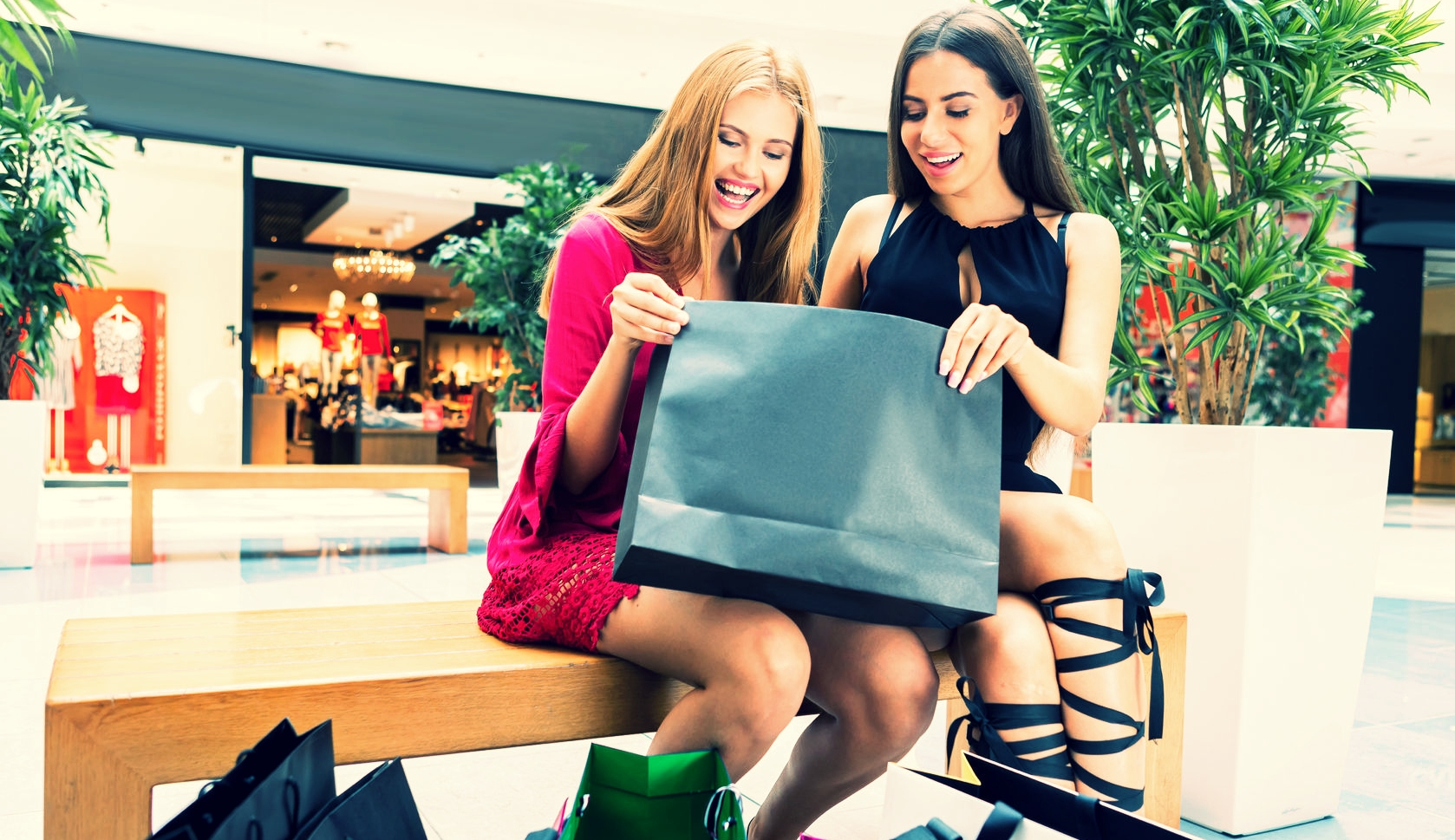 two-women-in-shopping-mall-with-a-black-bag