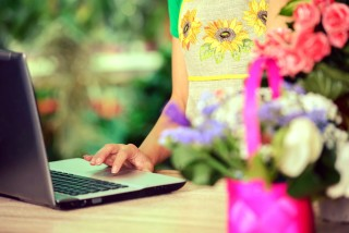Woman standing at laptop with flowers