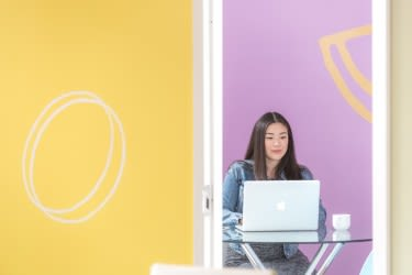 Woman sitting in front of yellow and pink walls with laptop