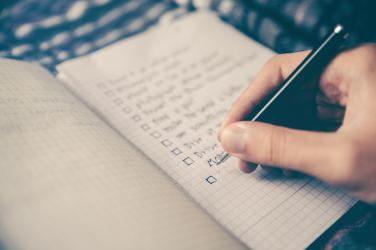 Someone writing a checklist in a notebook