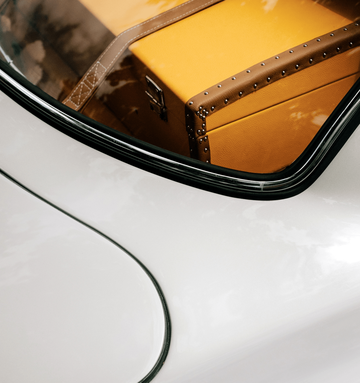 The back of a fancy white sports car showing a yellow retro suitcase
