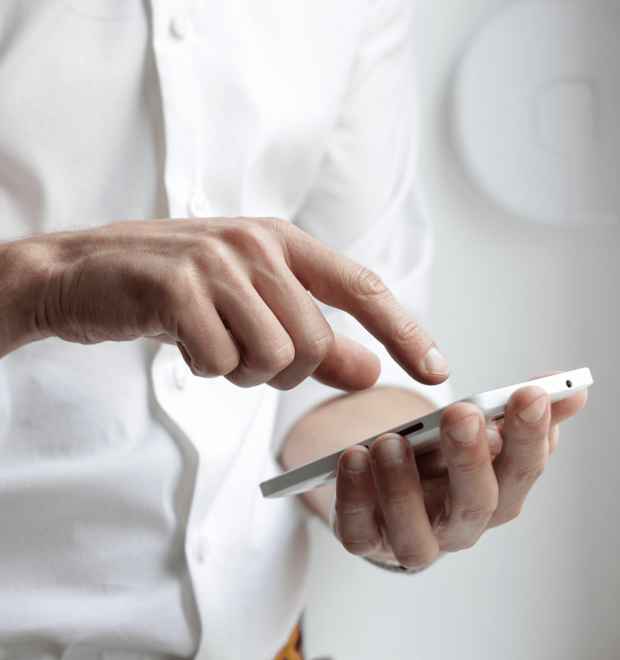 Photo of a man in a white shirt typing something on his smartphone