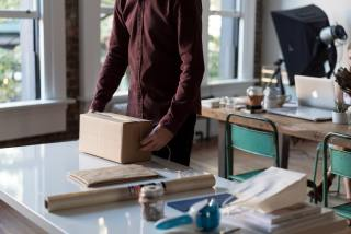 Picture of a man wrapping a box on a table