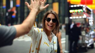 Picture of a woman with sun glasses smiling while she gives high five
