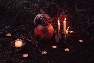 Pumpkin surrounded by candles at night