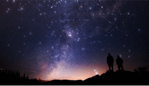 Two people outside looking at the universe