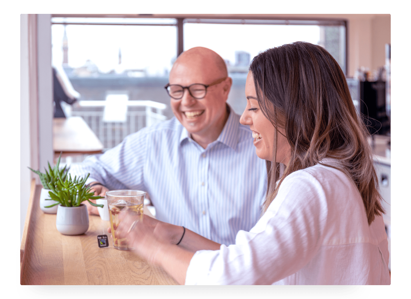 Photo of Trustpilot employees sitting and talking in the office's kitchen