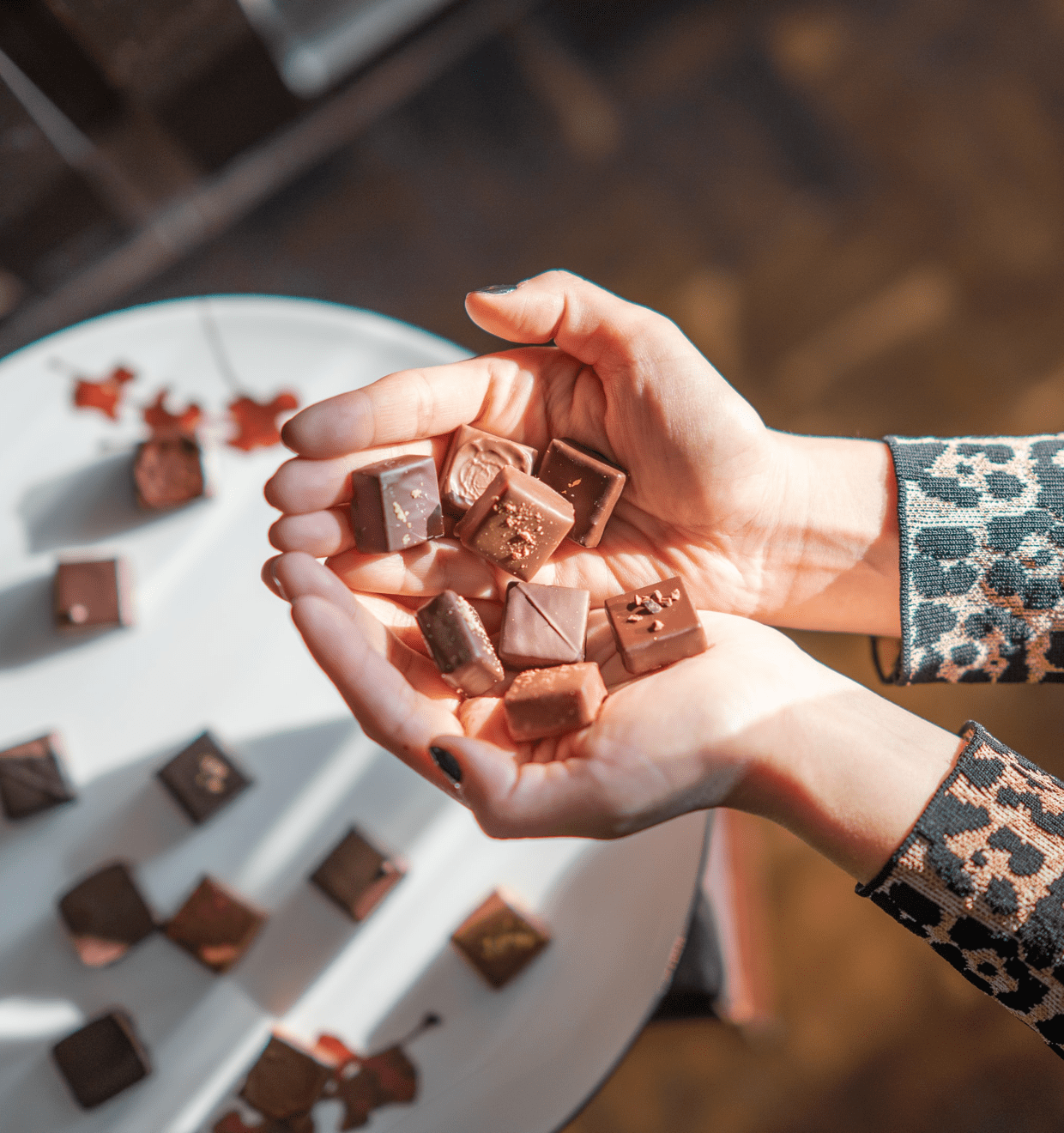 Photo of a woman's hands holding pieces of yummy looking chocolate above a plate with more chocolates