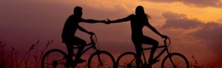 The power of trust - two people on bikes holding hands