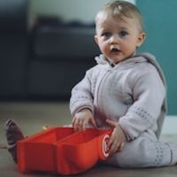 Infant sitting on floor playing with toy thumbnail