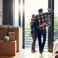 couple with packing boxes looking out window Thumb