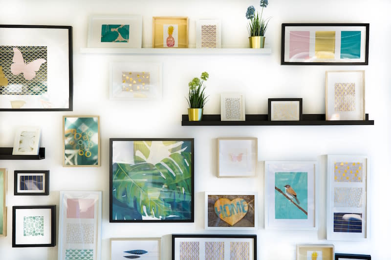 A colourful wall of stylish paintings in the home