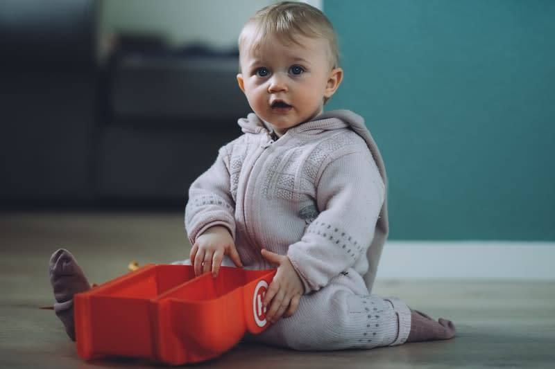 Infant sitting on floor playing with toy